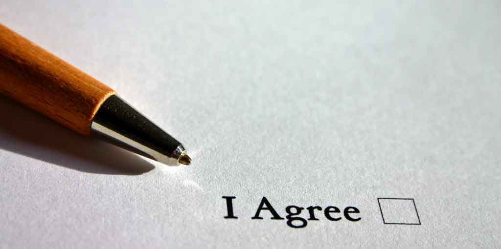 A pen held above a sheet of paper with the words ' I agree ' on it