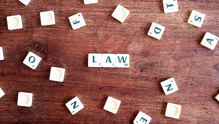 scrabble game pieces on a wooden surface spelling out 'law'