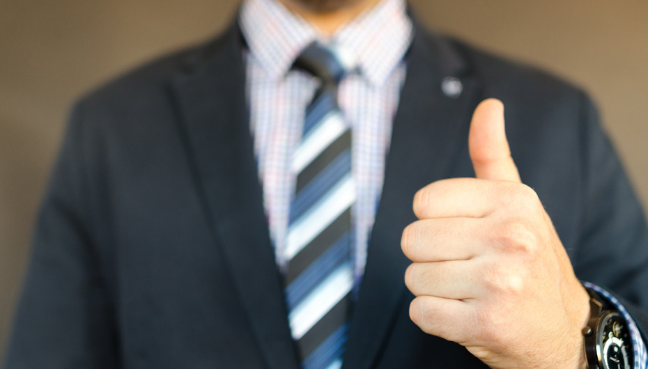 Man in a suit giving a thumbs up sign